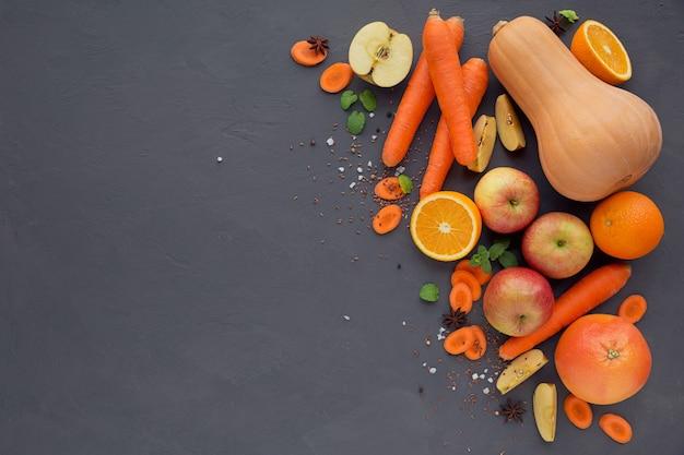 自家製ジュースまたはスムージー、果物と野菜のグラス。暗いテーブルに新鮮なニンジン、リンゴ、カボチャ、オレンジ、グレープフルーツ。健康的な食事、食事、ダイエット、デトックス、ベジタリアンのコンセプト。