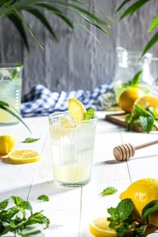 Стакан домашнего лимонада на белом фоне деревянных. вертикальный формат.