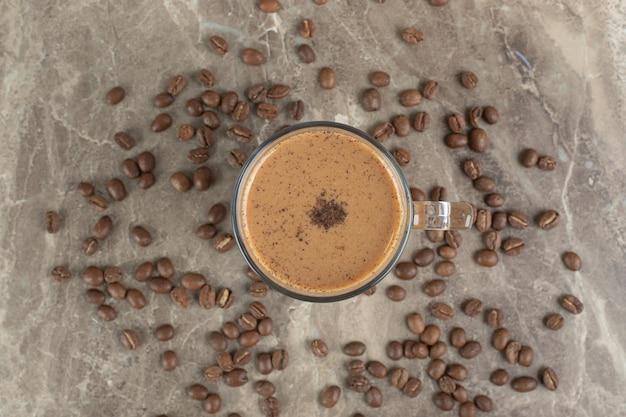 大理石の表面にホットコーヒーとコーヒー豆のガラス