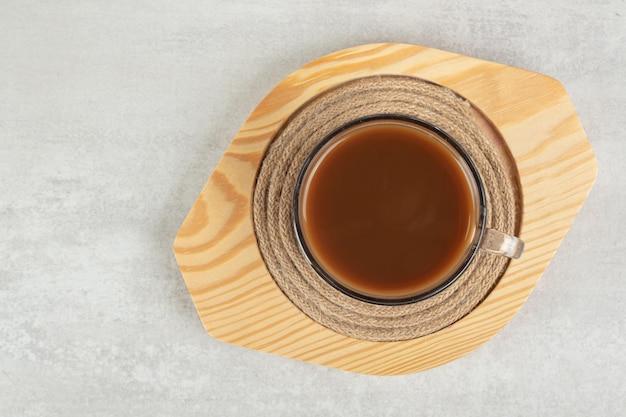 Стакан горячего кофе на деревянной тарелке.