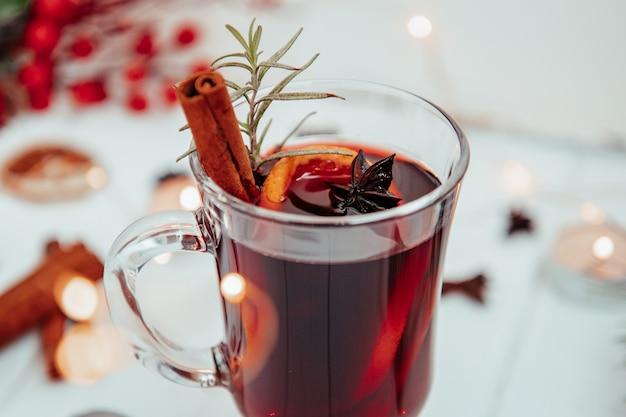 하얀 접시 클로즈업에 로즈마리와 함께 뜨거운 mulled 와인의 유리.