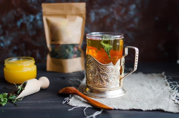 カップホルダーに熱いお茶、スプーンに蜂蜜とドライティーを入れたグラス