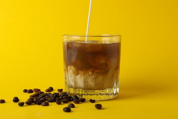 黄色の背景にアイスコーヒーのグラス。フレッシュドリンク