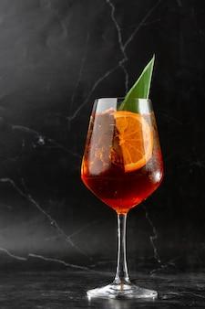オレンジのスライスで飾られたワイングラスで提供される氷のように冷たいアペロールスプリッツカクテルのグラス