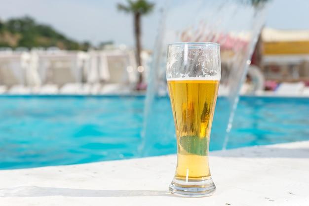 여름 휴가를 컨셉으로 한 열대 리조트의 청록색 수영장 가장자리에 있는 타일 위에 서 있는 차가운 맥주 한 잔