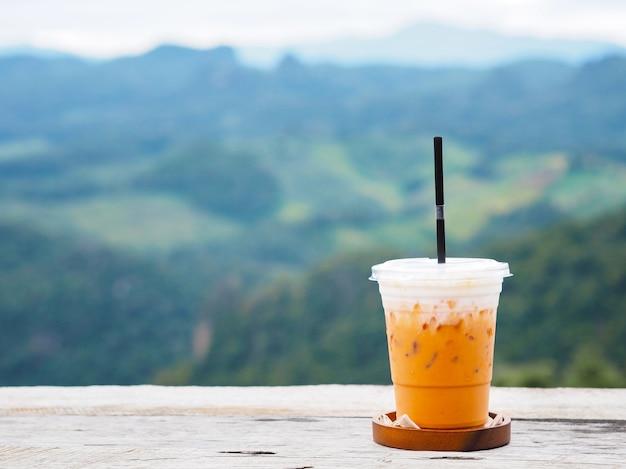 山の背景の緑の森の上のヴィンテージの木製テーブルにアイスミルクティーのガラス。