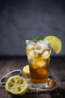 Стакан холодного чая с лимоном на деревянном столе