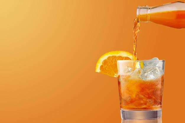 오렌지 조각으로 장식 된 아이스 콜드 분출 칵테일 잔. 아페리티프, coctail 만들기, 오렌지 배경에 고립 된 얼음이 가득한 유리에 액체를 붓는. 공간 복사