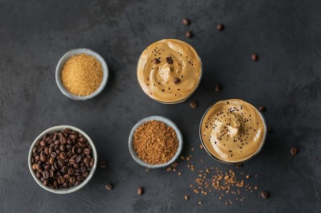 アイスダルゴナコーヒーのグラス、トレンディなふわふわのクリーミーなホイップコーヒーとブラックのミルク。