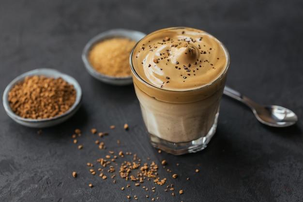 어두운 표면에 트렌디 한 푹신한 크림 휘핑 커피와 우유 인 아이스 달고나 커피 한잔