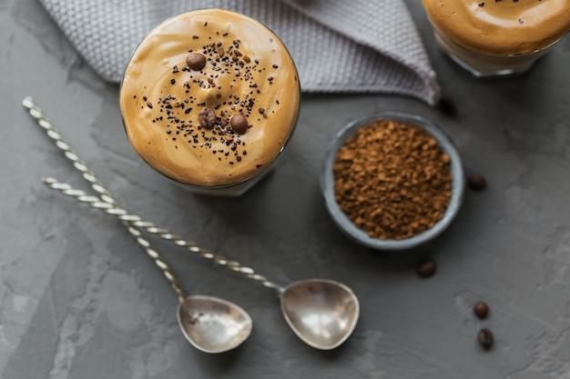 회색 표면에 트렌디 한 푹신한 크림 휘핑 커피와 우유 인 아이스 달고나 커피 한잔