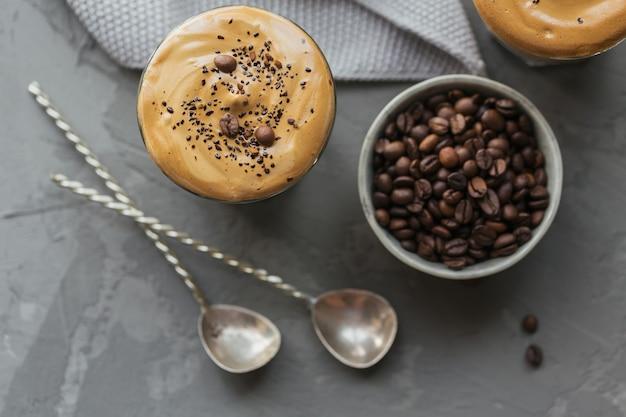 トレンディなふわふわのクリーミーなホイップコーヒーとグレーのミルク、アイスダルゴナコーヒーのグラス。