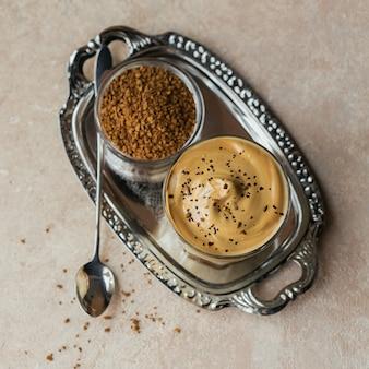 アイスダルゴナコーヒーのグラス、明るいベージュの背景にトレンディなふわふわクリーミーホイップコーヒーとミルク