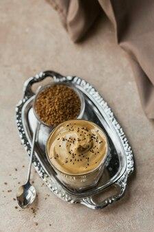 연한 베이지 색 표면에 트렌디 한 푹신한 크리미 한 휘핑 커피와 우유, 아이스 달고나 커피 한 잔