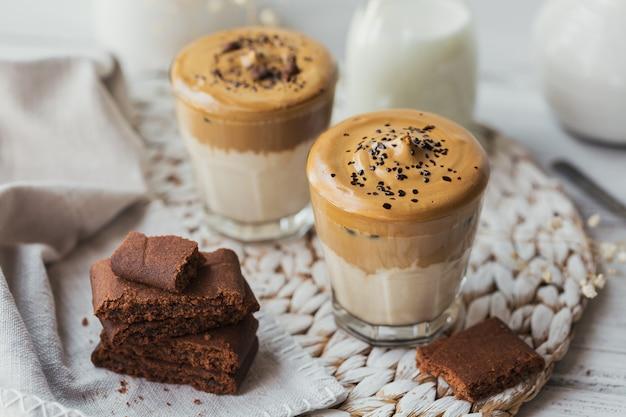 アイスダルゴナコーヒーのグラス、トレンディなふわふわのクリーミーなホイップコーヒーと白い木製のミルク。