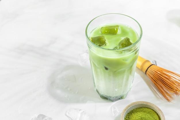 Стакан зеленого маття латте со льдом на поверхности белой плитки с жесткими тенями пальмовых листьев
