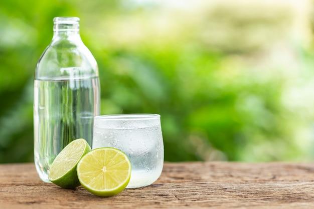 テキストまたはデザインの緑色のぼかしスペースと木製テーブルに氷のレモンソーダのガラス