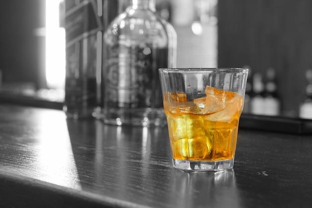 バーカウンターに立っているガラスのタンブラーの岩の上に氷のウイスキーのガラス、コピースペースでクローズアップ
