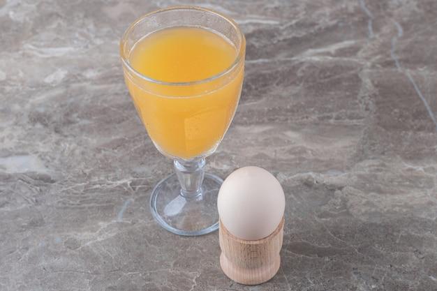 大理石のテーブルにジュースとゆで卵のガラス。