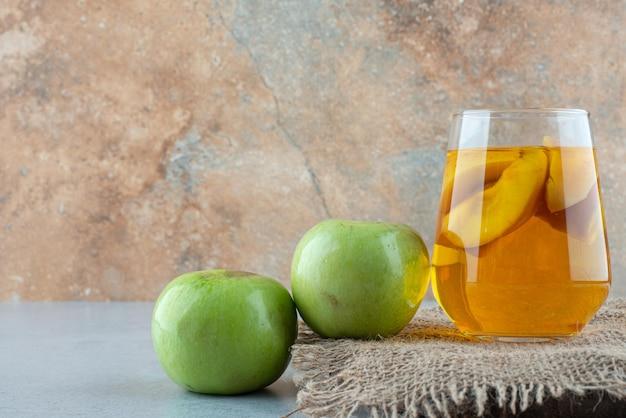 黄麻布にジュースと新鮮なリンゴのガラス。