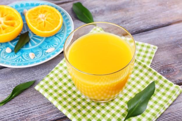 木製のテーブルにジュースと熟した甘いみかんのグラス