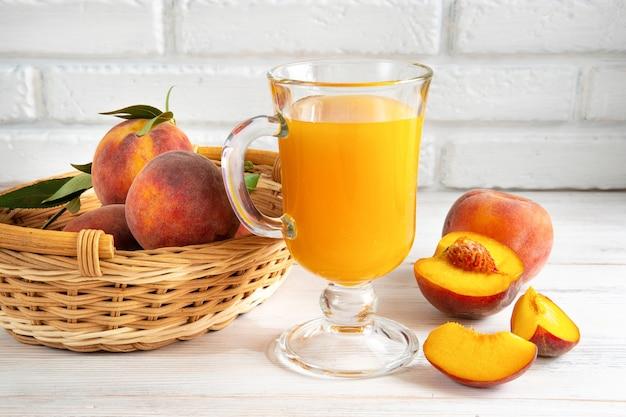 주스 한 잔과 달콤한 잘 익은 달콤한 과일, 배경에 바구니에 녹색 잎이 있는 복숭아