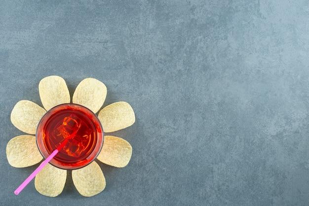 대리석 배경에 감자 칩으로 둘러싸인 주스 한 잔. 고품질 사진