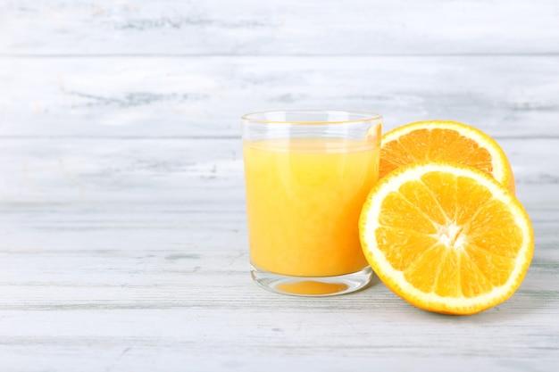 Стакан сока со свежим апельсином на сером деревянном столе