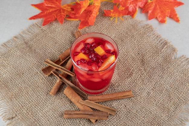 삼 베에 과일 조각과 계피 스틱 주스 한 잔.
