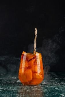 Стакан сока с кусочками айвы и соломой на мраморном столе