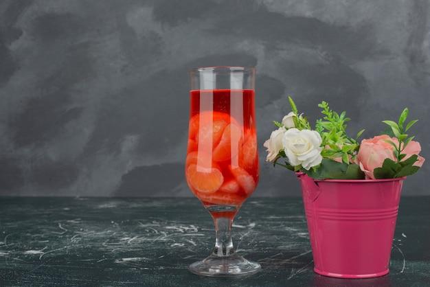 大理石のテーブルに小さなバケツとジュースのガラス。