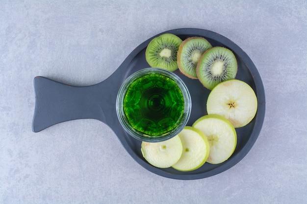 大理石のテーブルの上に、鍋にキウイジュースとリンゴのグラス。