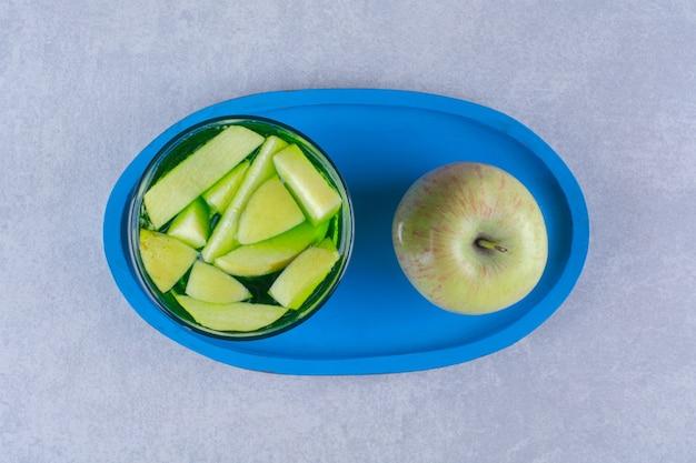 대리석 테이블에 있는 나무 접시에 키위 주스와 사과 한 잔.