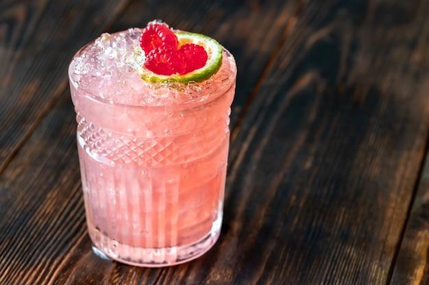 ラム酒、ライムジュース、オレンジキュラソー、ラズベリーシロップで作られたニッカーボッカーカクテルのグラス Premium写真