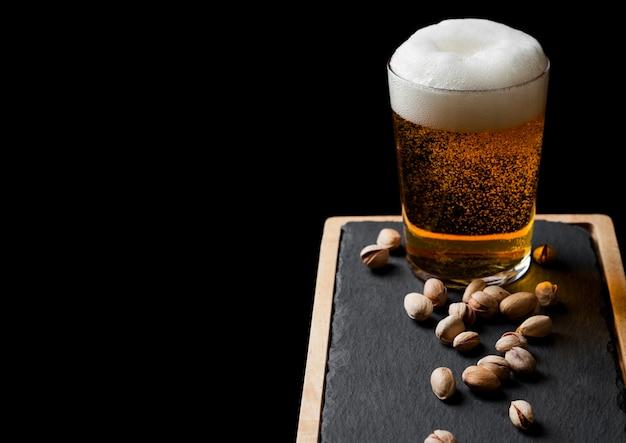 블랙에 돌 보드에 피스타치오 너트와 라 거 맥주 한 잔