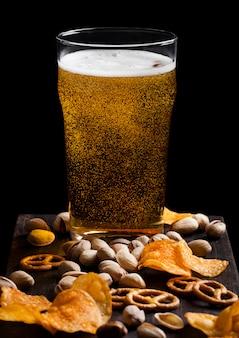 블랙 빈티지 나무 보드에 간식으로 라 거 맥주 한 잔.