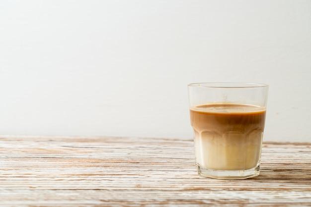 ラテコーヒーのガラス、木製のテーブルにミルクとコーヒー