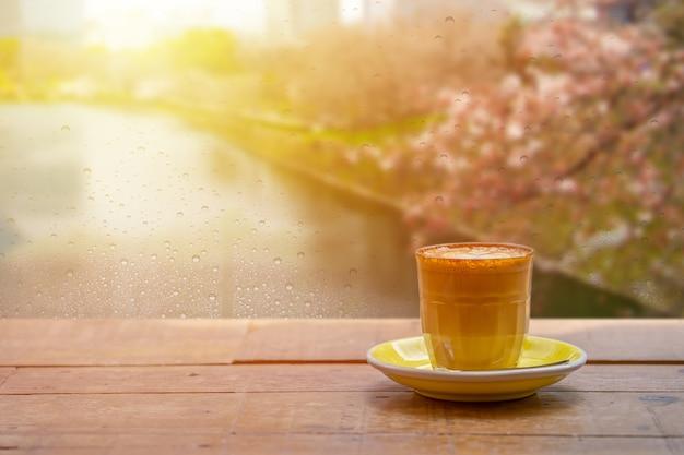 아침에 비가 온 후 빗방울이 떨어지는 창문 가까이에 라떼 아트가 있는 라떼 한 잔