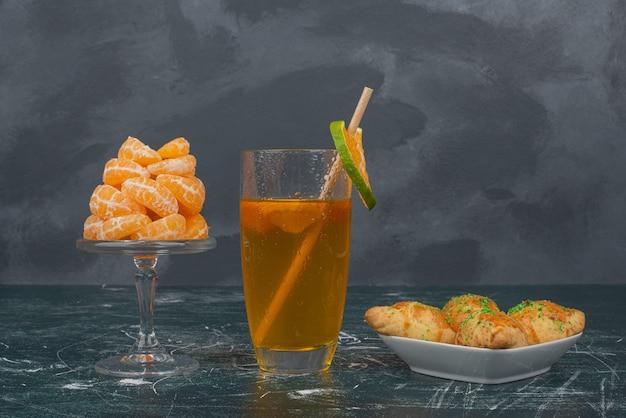 Стакан лимонной воды с тарелкой сладкой выпечки и дольками мандарина.
