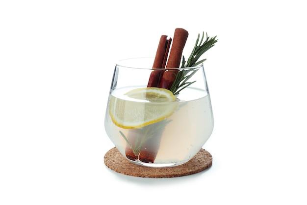 白い表面に分離されたシナモンとローズマリーとレモネードのガラス