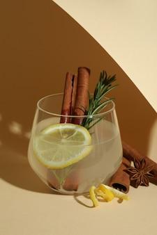ベージュの表面にシナモンとローズマリーのレモネードのガラス