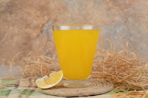 Стакан лимонада с долькой лимона на скатерти