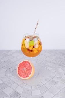 Стакан лимонада с ломтиком грейпфрута и соломой.