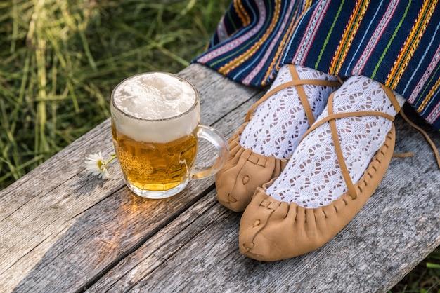 軽めのビールと革靱皮の女性靴のガラス