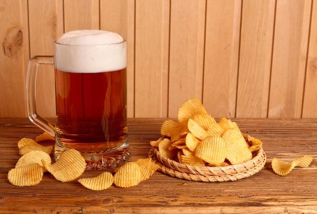 Стакан светлого пива и картофельные чипсы на деревянном столе