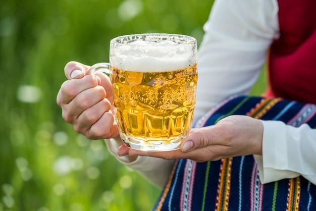 女性の手で軽いビールのグラス。