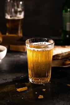 黒いテーブルの上の軽いビールのガラス