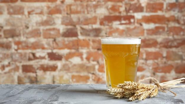 白い石の背景に軽いビールのガラス。仲良しのパーティーのために、冷たいお酒とお肉のおやつを用意しています。