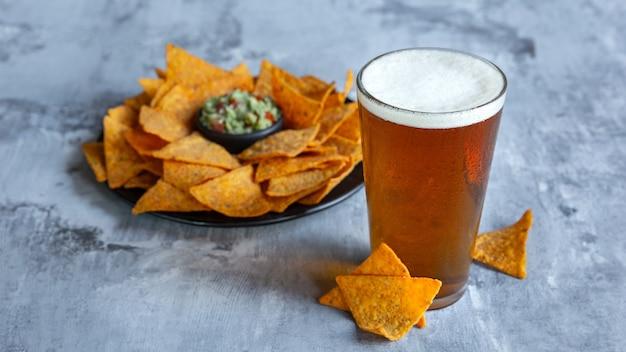 白い石の表面に軽いビールのグラス。大きな友達のパーティーのために、冷たいお酒と軽食が用意されています。