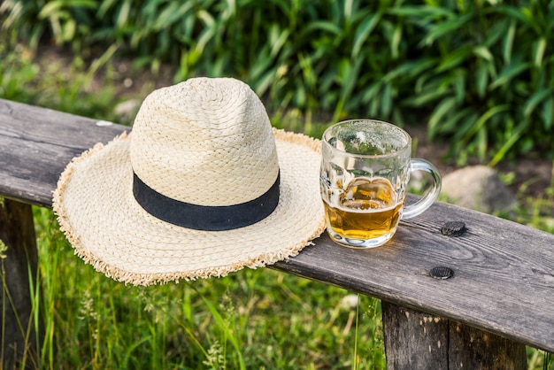 ベンチに織りの帽子と軽めのビールのグラス